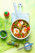 Shakshuka with green asparagus, beans and peas