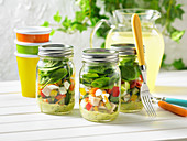 Salad in glass jars with chicken, spinach and eggs