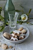 Zimtsterne, Vanillekipferl und Schnapsgläser auf Teller