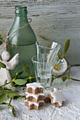 Zimtsterne, Schnapsgläser und Zwetschgenwasser in grüner Flasche