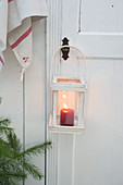 Lit candle in lantern hung from wooden door