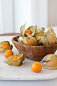 Physalis (Cape gooseberries) in a wooden bowl and next to it