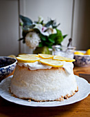 Angel food cake with whipped cream and lemon slices, with flowers, a jar of whipped cream, and bowl of lemons in the background
