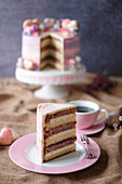 A berry cake with white chocolate and macaroons, sliced