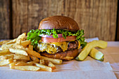 Cheese burger with lettuce tomato, onion, pickle and french fries