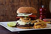 Burger mit Blauschimmelkäse, Kopfsalat, frittierten Zwiebeln, Essiggurke und Tomate, dazu Pommes