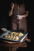 Challah-Brot (jüdische Küche) zubereiten: Hefezöpfe mit Butter bepinseln