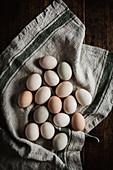Mit Naturfarben gefärbte Eier auf Leinentuch (Aufsicht)