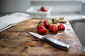 Strawberries on Wood Cutting Board with Knife and Towel