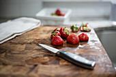 Erdbeeren auf Holzbrett mit Messer und Küchentuch