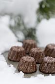 Mini Schokoladen-Guglhupf mit Schnapsglasur auf Tablett im Schnee