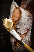 A piece of pain d'Epi (French baguette shaped like an ear of wheat) and a knife with butter