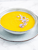 Vegan pear, carrot and pumpkin soup, served with edible rosemary flowers
