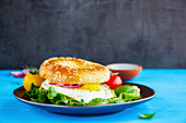 A bagel with a fried egg, lettuce and tomatoes
