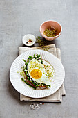 A spring sandwich with green asparagus, a fried egg, feta cheese and beansprouts