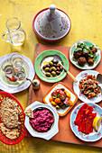 Buffet mit Mutabal, Oliven, gerösteten Paprikaschoten, Tomatensalat, Rote-Bete-Hummus und Fladenbrot