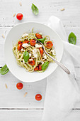 Pasta with tomatoes, mozzarella, pine nuts and basil