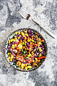 Bunter Quinoasalat mit Tomaten, Mais, Edamame, Rotkohl, gerösteten Kichererbsen und Karotten
