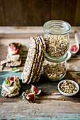 Festive dukkah in a jar as a gift served with low carb seeded crackers, figs, cream cheese and basil