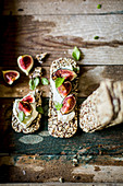 Low carb seeded crackers, figs, cream cheese and basil on a rustic wooden surface