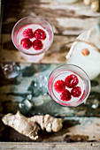 Festive gingerbeer in bottles and glasses served with raspberries on a rustic wooden surface with ice