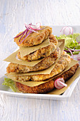 Cooked and breaded cutlets, stacked on a dish