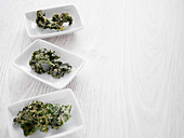 Kale chips in white bowls on a wooden board