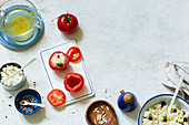 An arrangement of stuffed tomatoes and ingredients