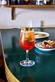 Ein Aperol Spritz im Glas mit Olivenspiesschen