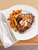 Steak with baked kumara chips and olive salsa