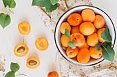 Apricots in a bowl and on a flowered cloth
