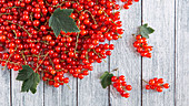 Redcurrants with leaves on wooden background