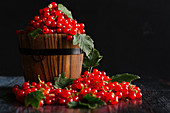 Redcurrants with leaves in and around a wooden basket