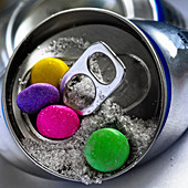 A soft drink can with colorful chocolate beans