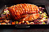Pork roast with vegetables on a baking tray