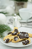 Piped biscuits with chocolate glaze on a table laid for coffee and decorated for Christmas