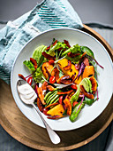 Salad with vegetables, fruit and marinated coconut chips