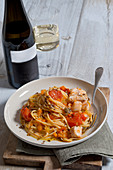 Linguine with fish ragout, cherry tomatoes, oranges and roasted capers