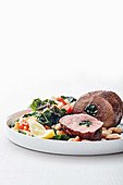Stuffed roast lamb served with chard and white beans
