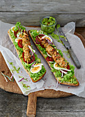 Chicken kebabs on ciabatta with an avocado dip, lollo bionda lettuce, tomatoes and hard-boiled eggs