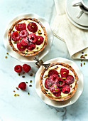 Raspberry tartlets with vanilla pudding on a marble platter