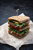 A vegan sandwich with grilled peppers, rocket and cheese substitute