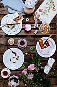 Gedeckter Tisch mit Brocante-Dekoration im Freien