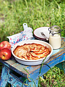 Apple pie in a baking tin, with a glass jar of cream next to it