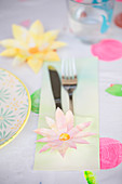 Cutlery pouch decorated with paper flowers on table