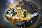 Roast fish with Asian spices in a wok