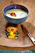Potato and buttermilk soup with fried egg yolk on oriental spinach