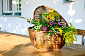 A basket of flowers on a wooden table in front of a house