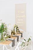 Tulpenstrauß, trockenen Zweigen und Cylinderkerzen, im Hintergrund Botschaft an der Wand