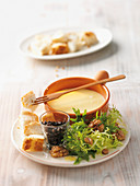A mini cheese fondue with endive salad and beluga lentils